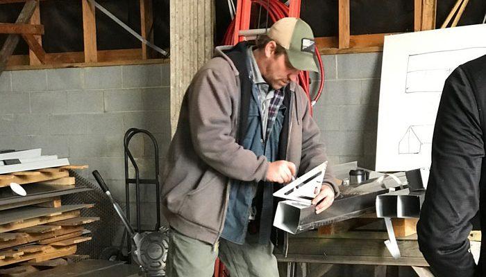Man measuring custom sheet metal fabrication